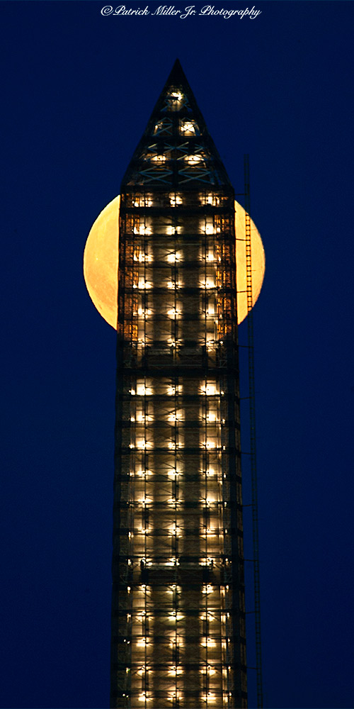 Super Full Moon rising directly behind the top of the lighted Washington Monument during renovations, DC