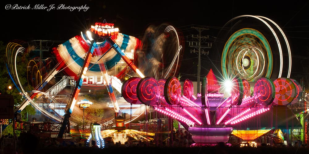 Traveling carnival rides at night in motion with vivid colors