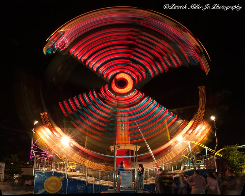 Traveling carnival Tomahawk ride in motion producing a red circle