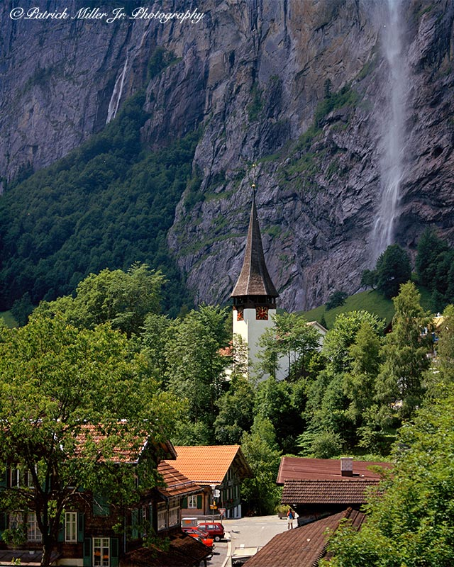 Small Swiss town with steeple and waterfalls