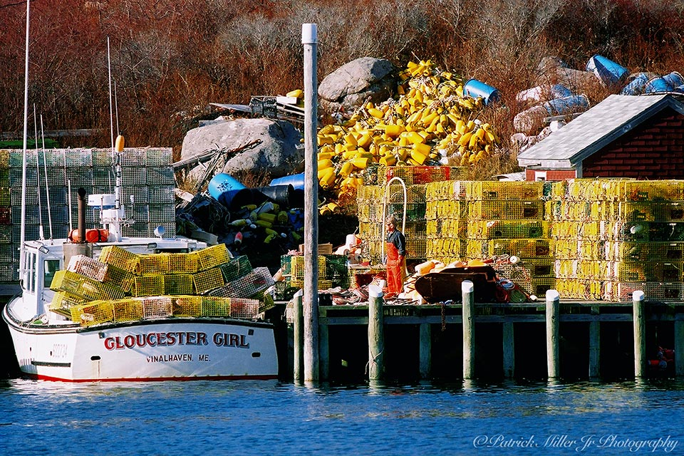 "Lobsterman on his dock full of colorful lobster equipment and his lobster boat ""Gloucester Girl"""