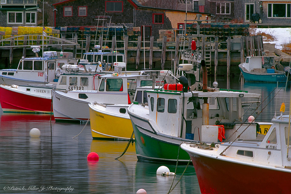 Colorful lobster boats closely lined up in busy Carvers Harbor Maine
