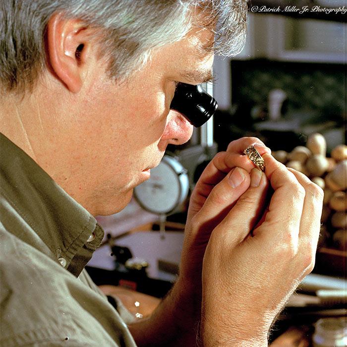 Jewelry maker inspecting a diamond ring, San Francisco, CA