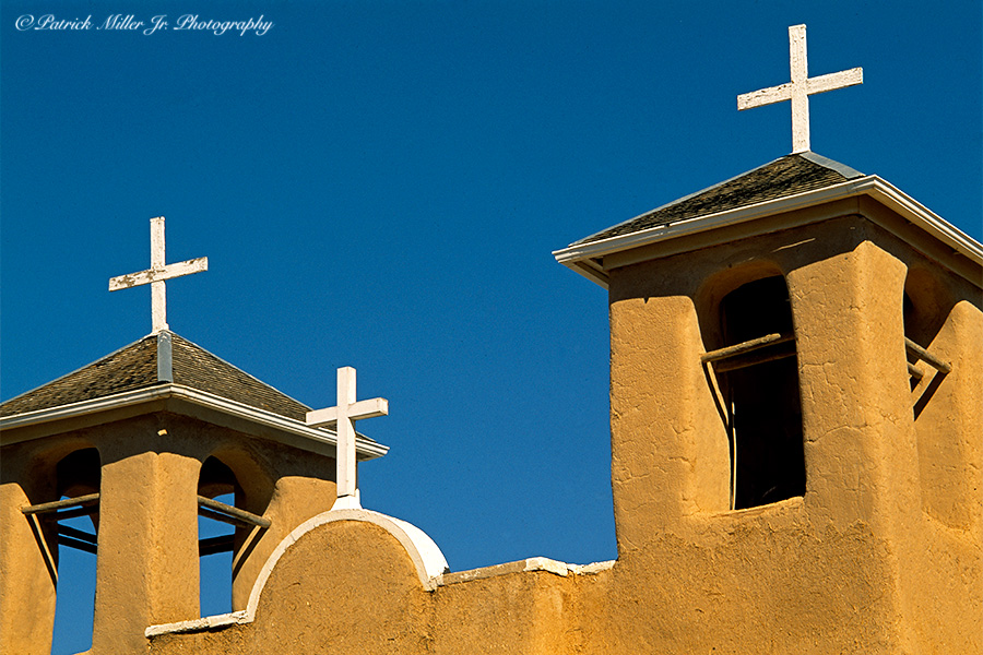 Adobe style stucco steeples with white crosses Christian Mission Church Santa Fe New Mexico