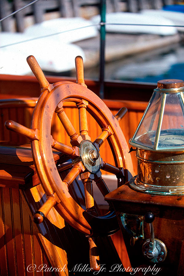Restored wooden yacht with wooden wheel and brass compass, Maine